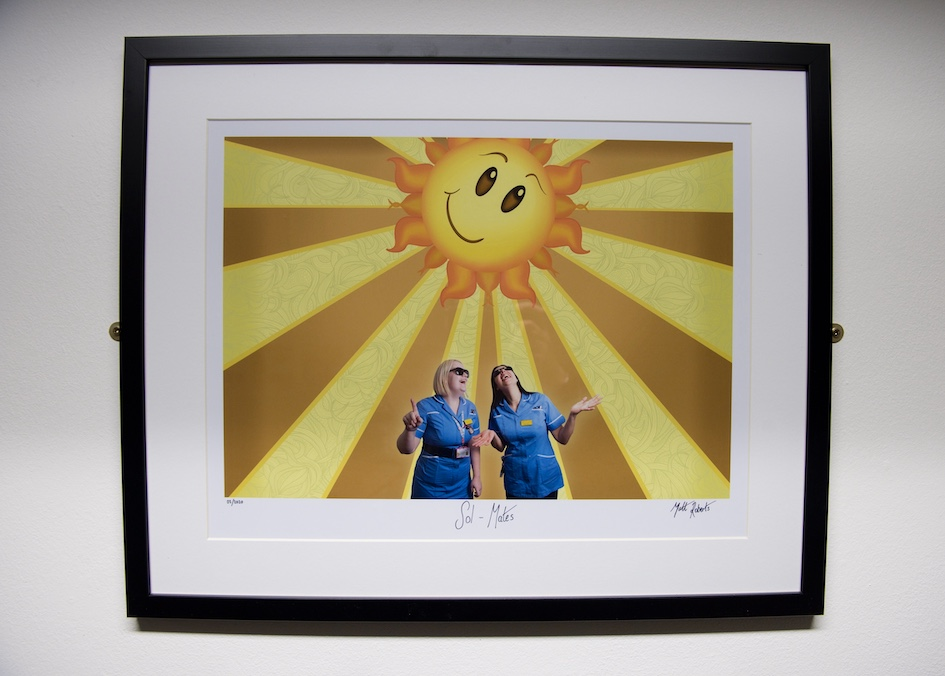 Image of two nurses with a cartoon sun behind them, by Matt Roberts, from Air Arts' Wellbeing in the Workplace exhibition