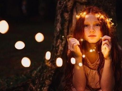 picture of a young woman with a string of lights