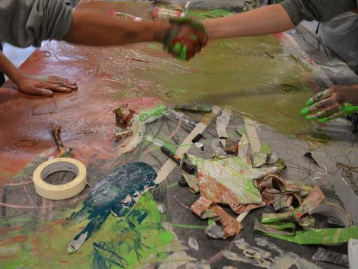 Photo of two people shaking hands, with their hands covered in paint after an art workshop