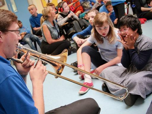 A trombonist plays for two schoolgirls
