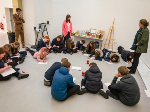 A group of teenagers seated on the floor during a workshop run by Claire Newton