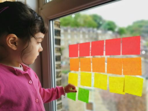 A young girl plays with coloured post-its on a window